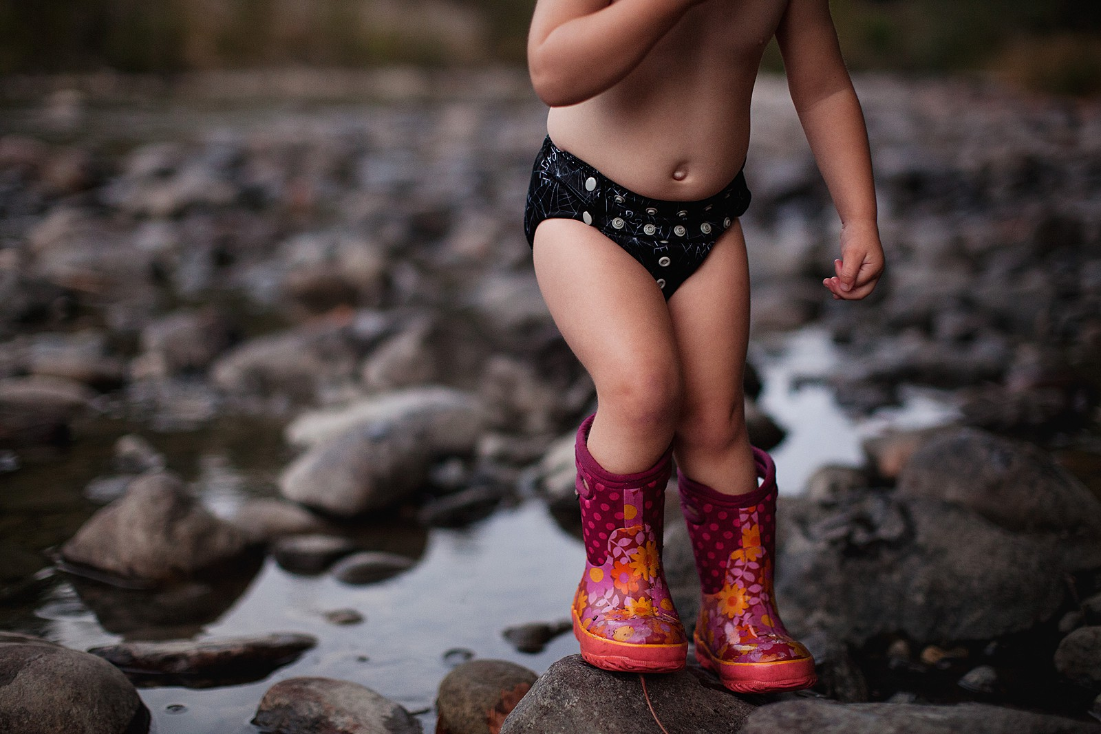 Outdoor_adventures_Neyssa_Lee_6 young child in boots and diaper outside on river bank