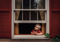 boy eating apple looking out window with red shutters by meg loeks