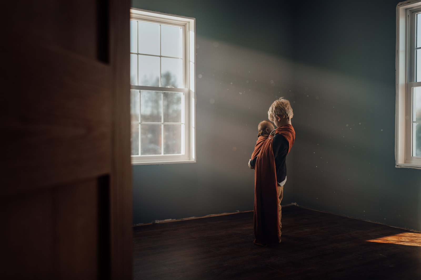 boy holding baby by window with light beams meg loeks