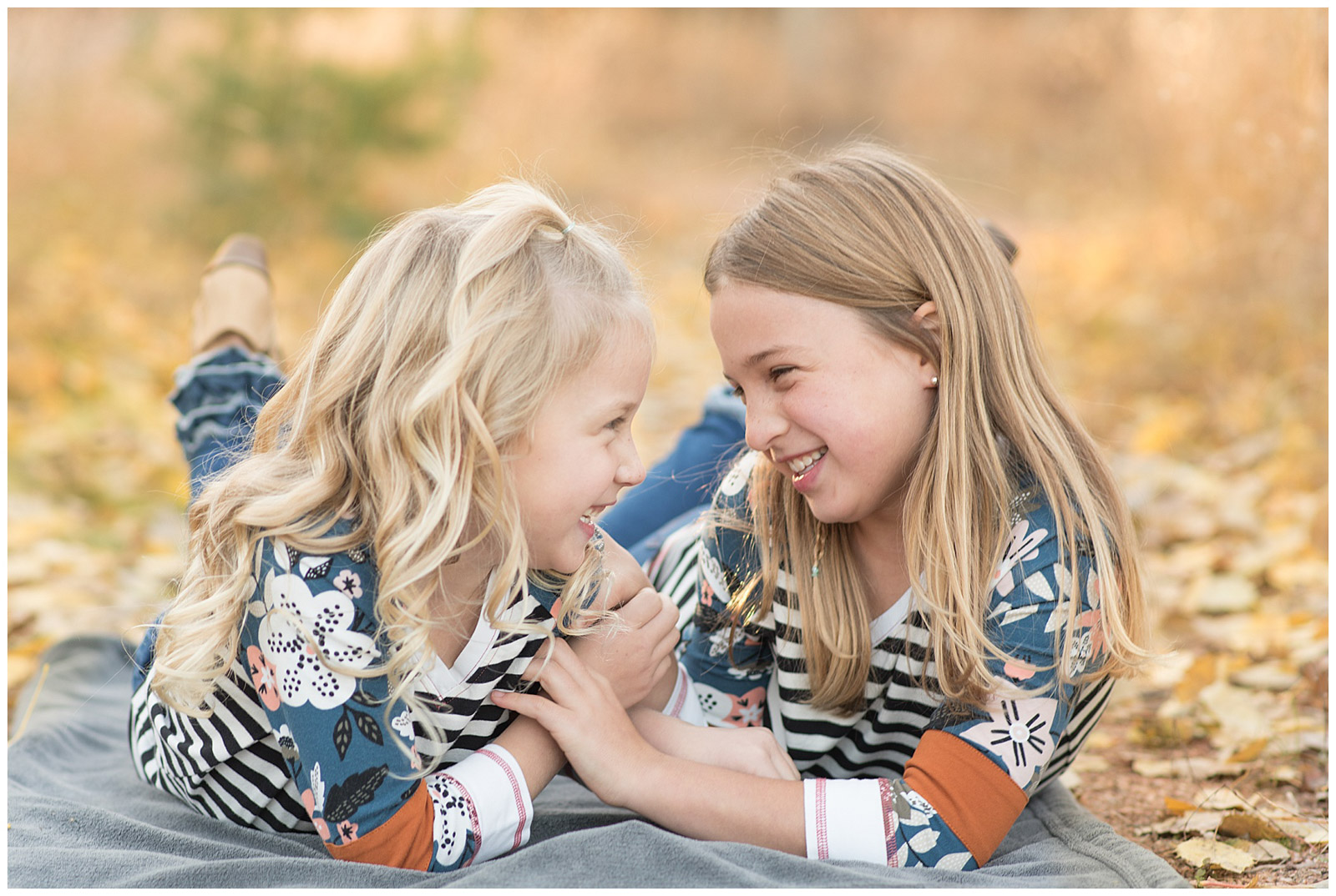 girls smiling together outside on blanket emily and erin drew esquared photography
