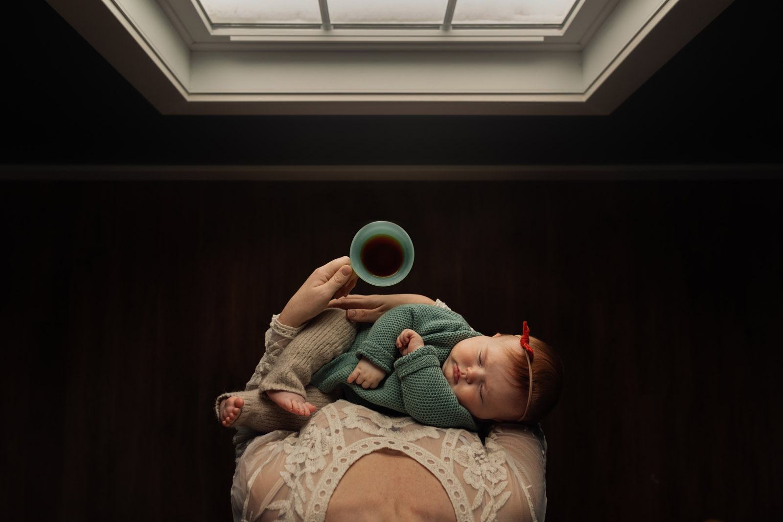 mom holding baby and cup of coffee by window meg loeks