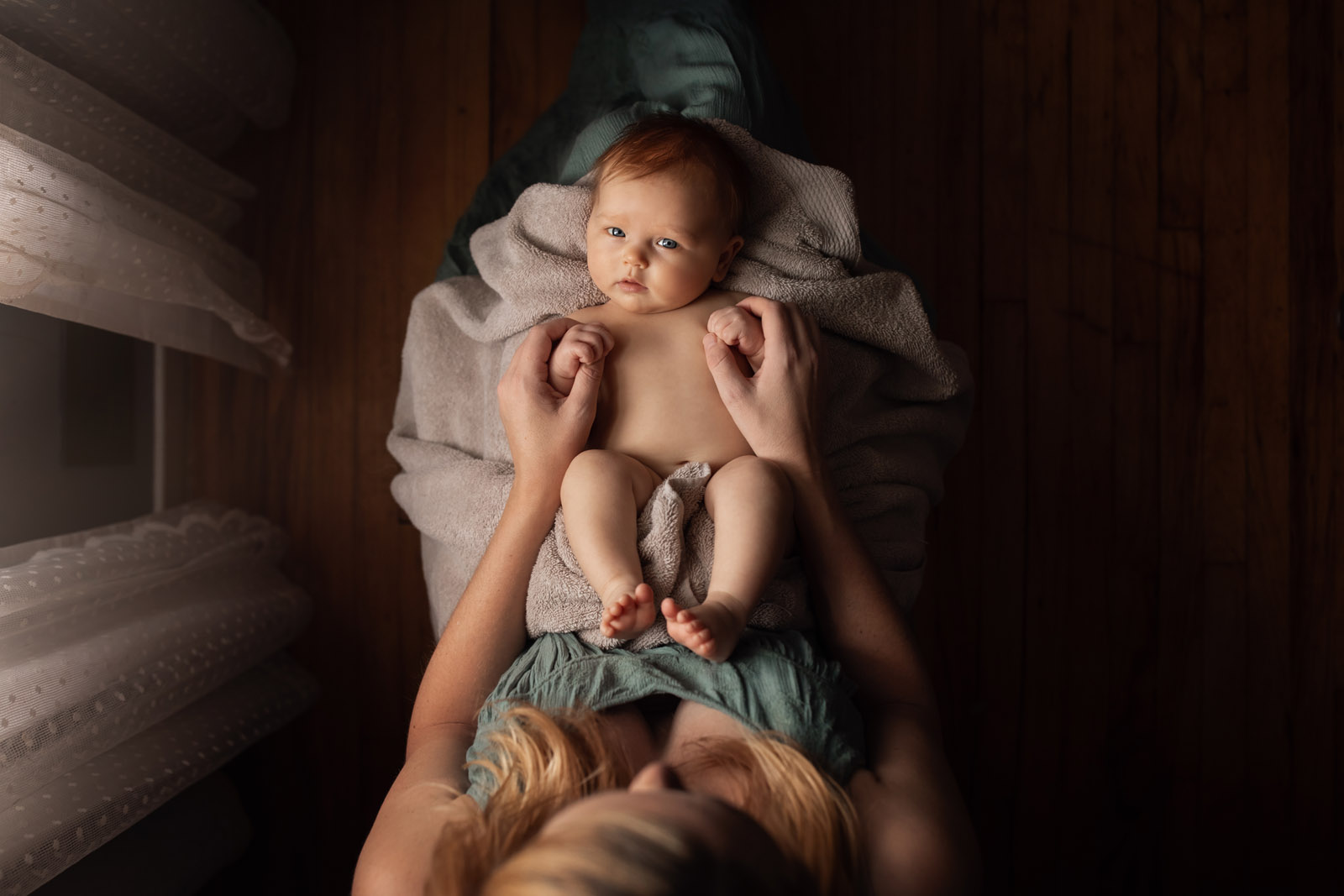 mother holding baby on lap by window catchlights by meg loeks