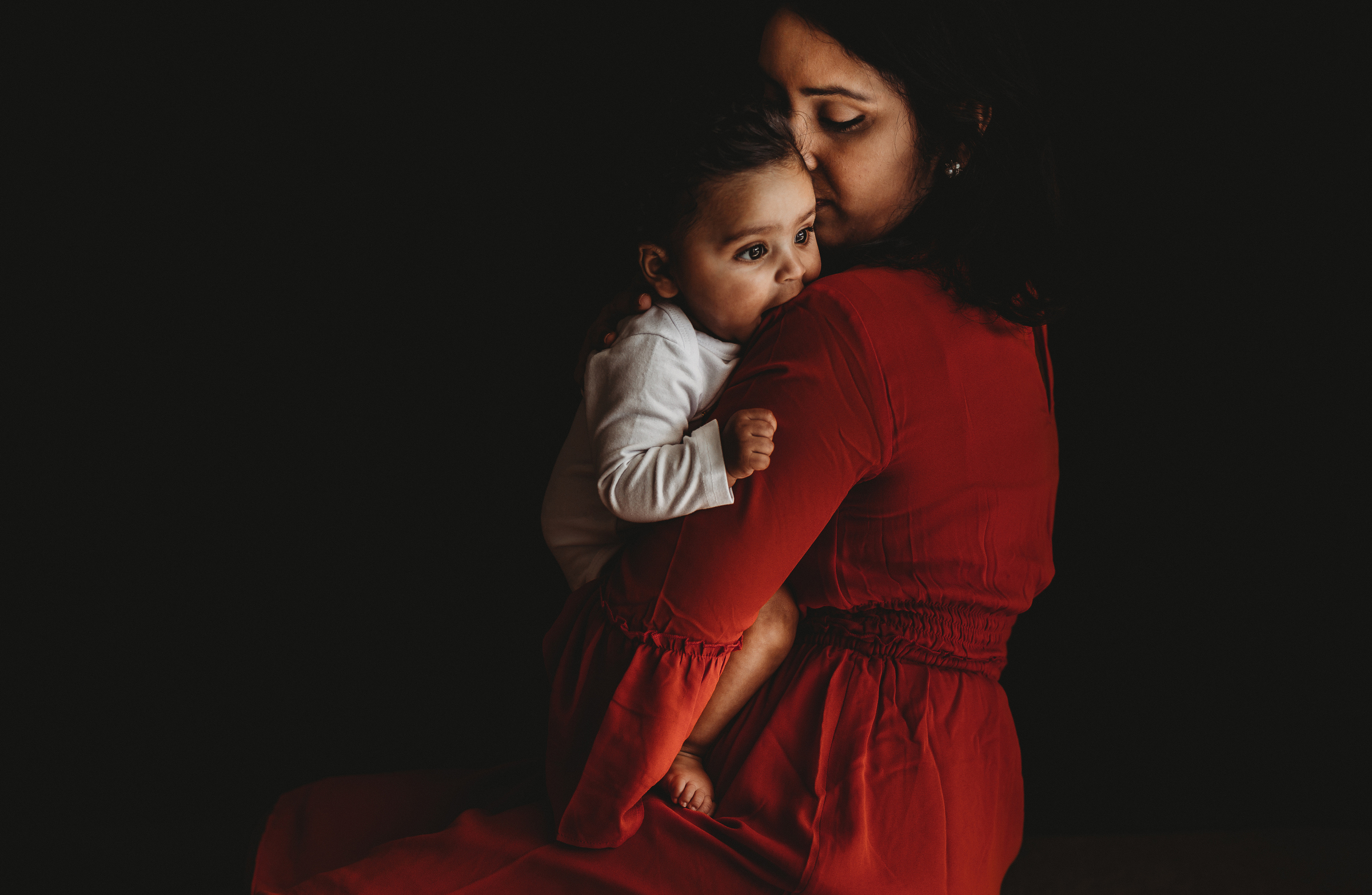 mother in red dress kissing baby self portrait jyo bhamidipati