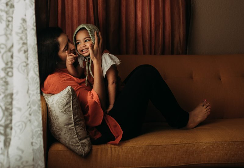 mother kissing small child in bonnet on sofa self portrait jyo bhamidipati