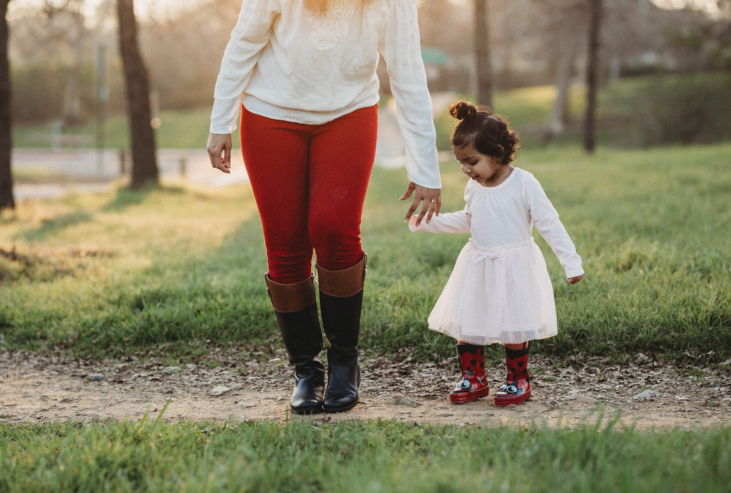 toddler girl in dress and boots walking outside with mother in red pants self portrait jyo bhamidipati