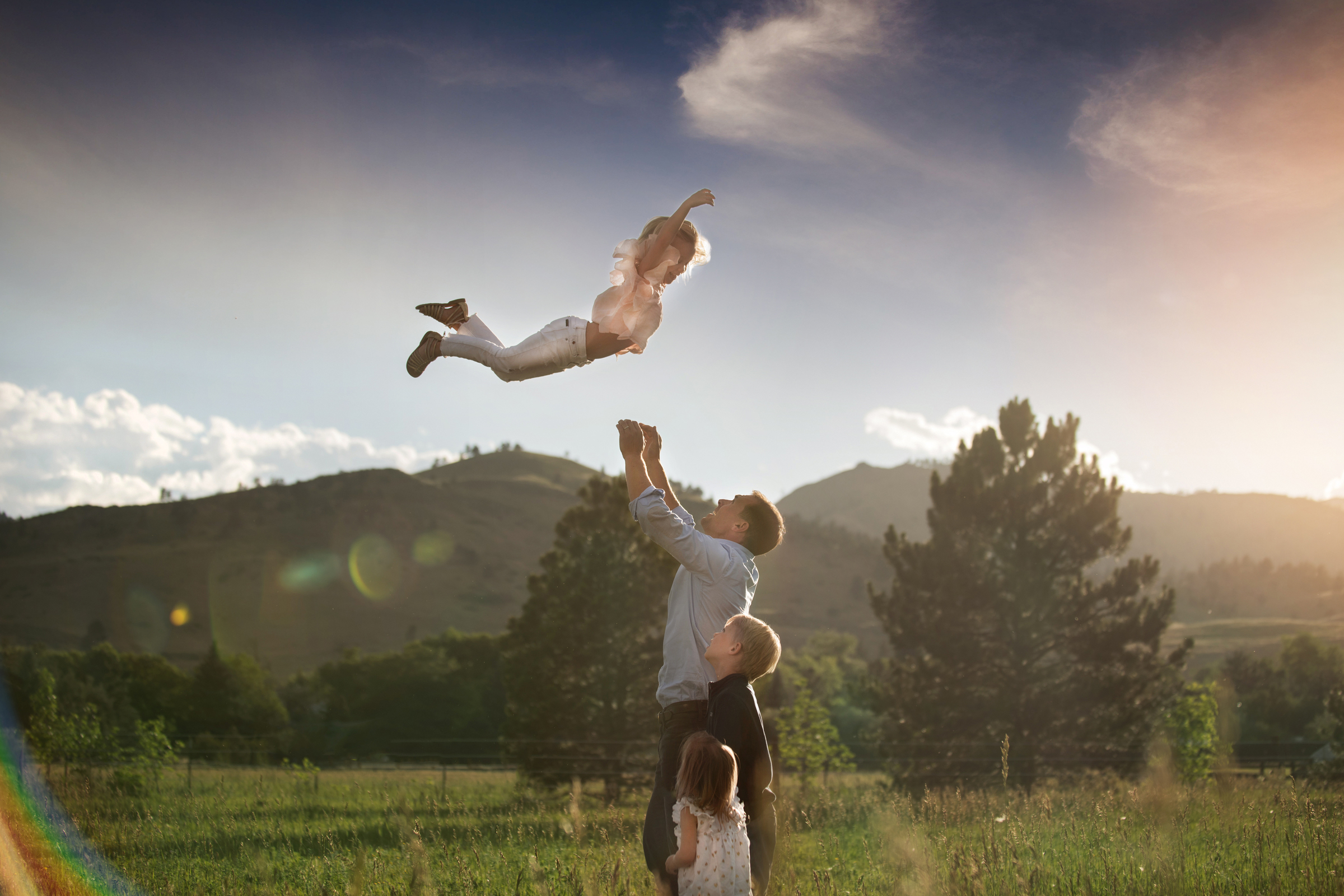 dad throwing child in air as kids look on fathers day d'ann boal