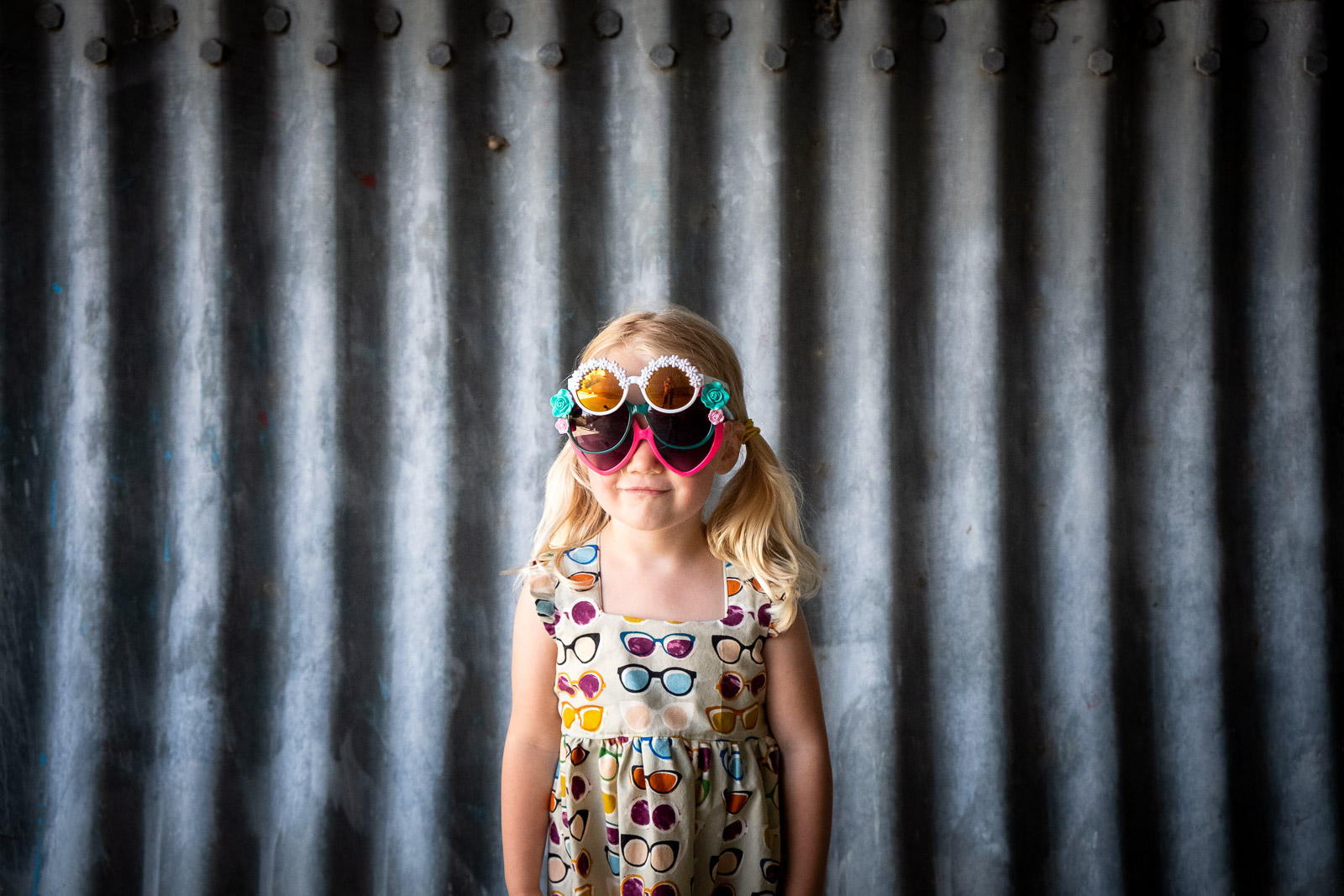 Unexpected Backdrop- corrugated metal wall girl with three pairs of sunglasses karlee hooper