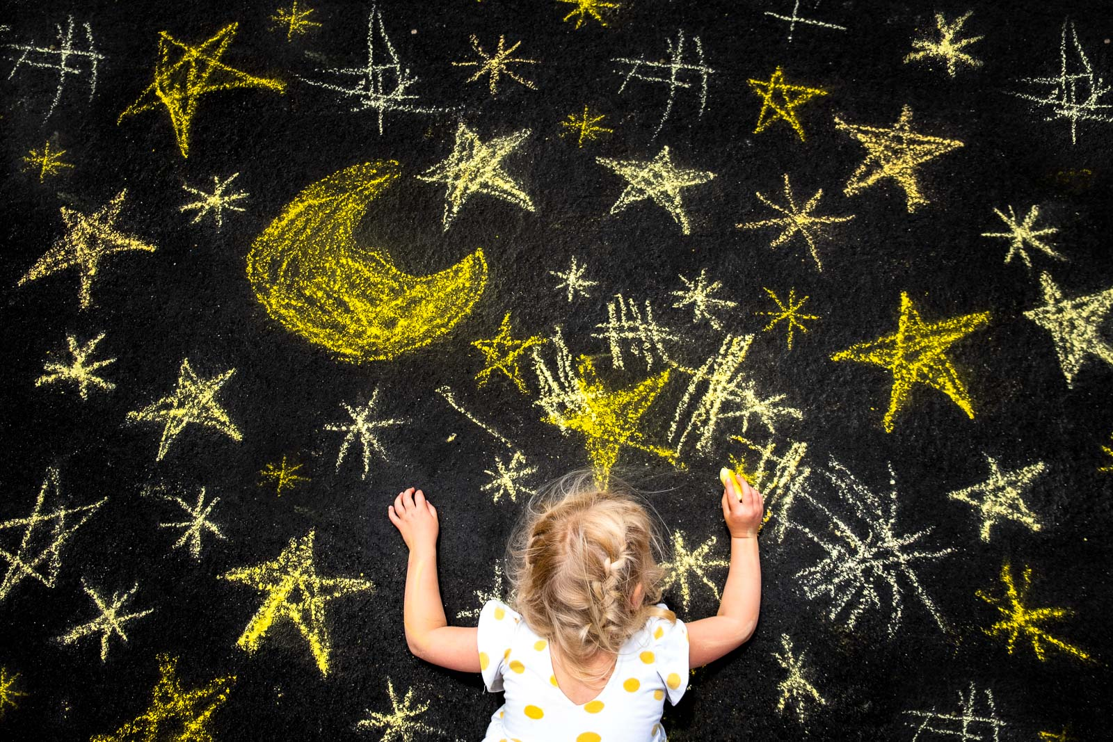Unexpected Backdrop girl drawing yellow stars on black asphalt by karlee hooper