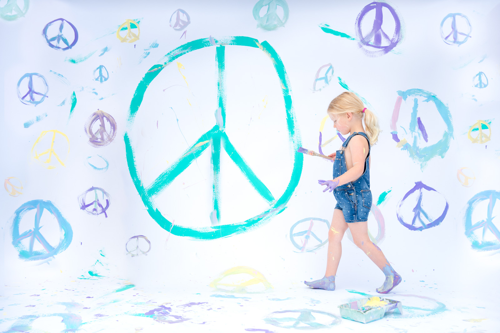 Unexpected Backdrop girl in overalls painting peace signs karlee hooper