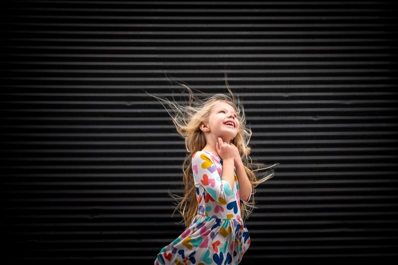 Unexpected Backdrop girl with hair blowing in front of black striped wall karlee hooper
