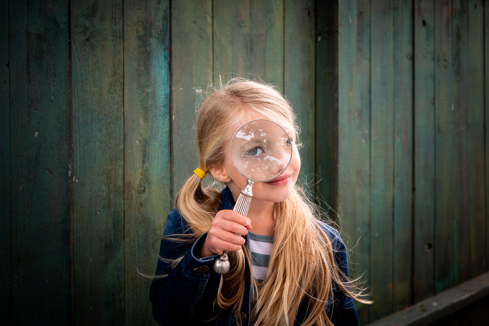 Unexpected Backdrop girl with magnifying glass in front of green fence by karlee hooper