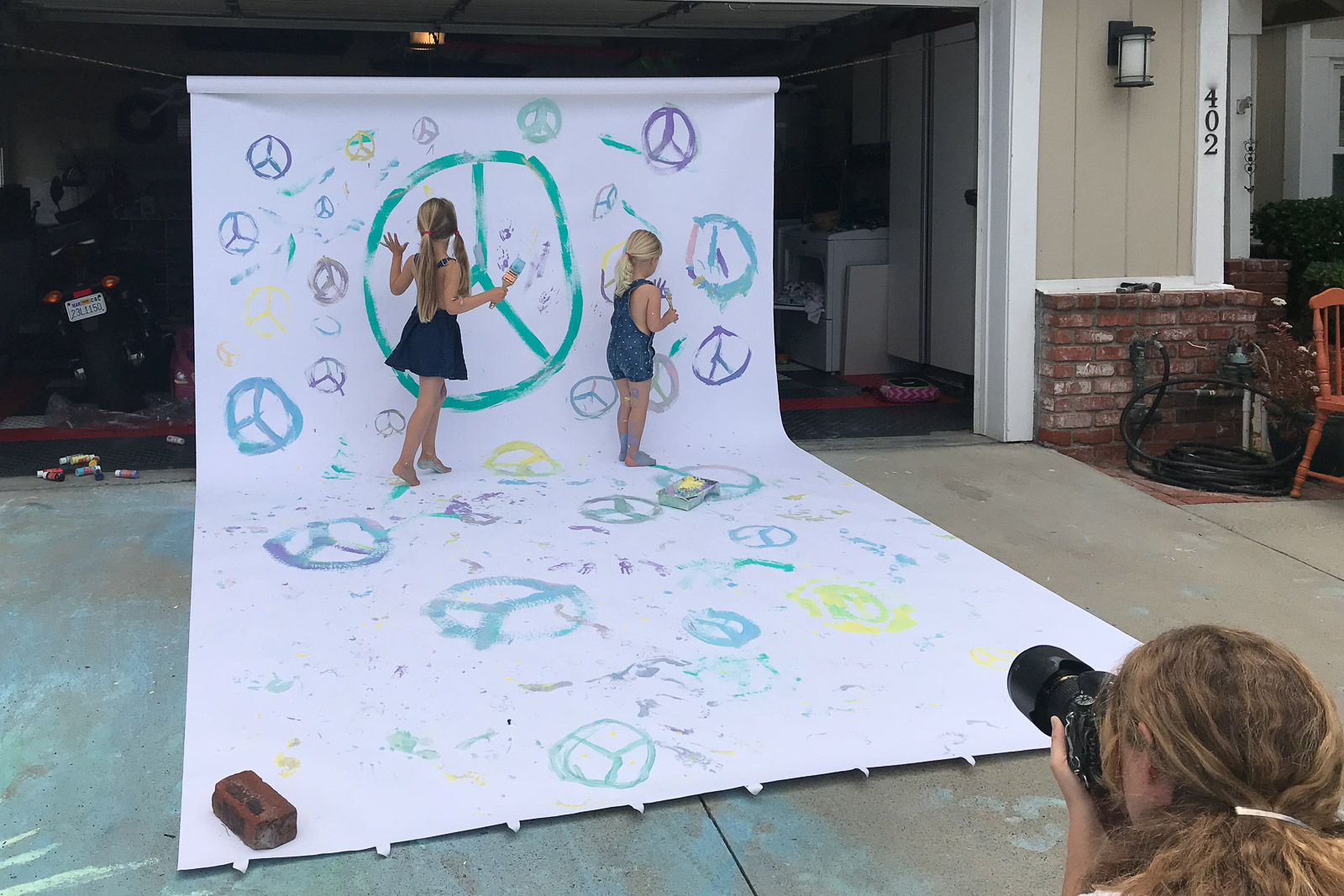 Unexpected Backdrop pullback of kids painting peace signs on large paper karlee hooper