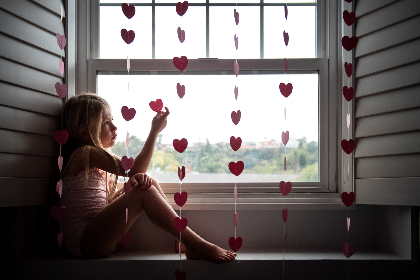 Unexpected Backdrops Window decorated with heart garland karlee hooper