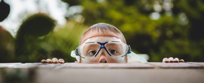 boy in goggles peeking over edge of pool natalie greenroyd