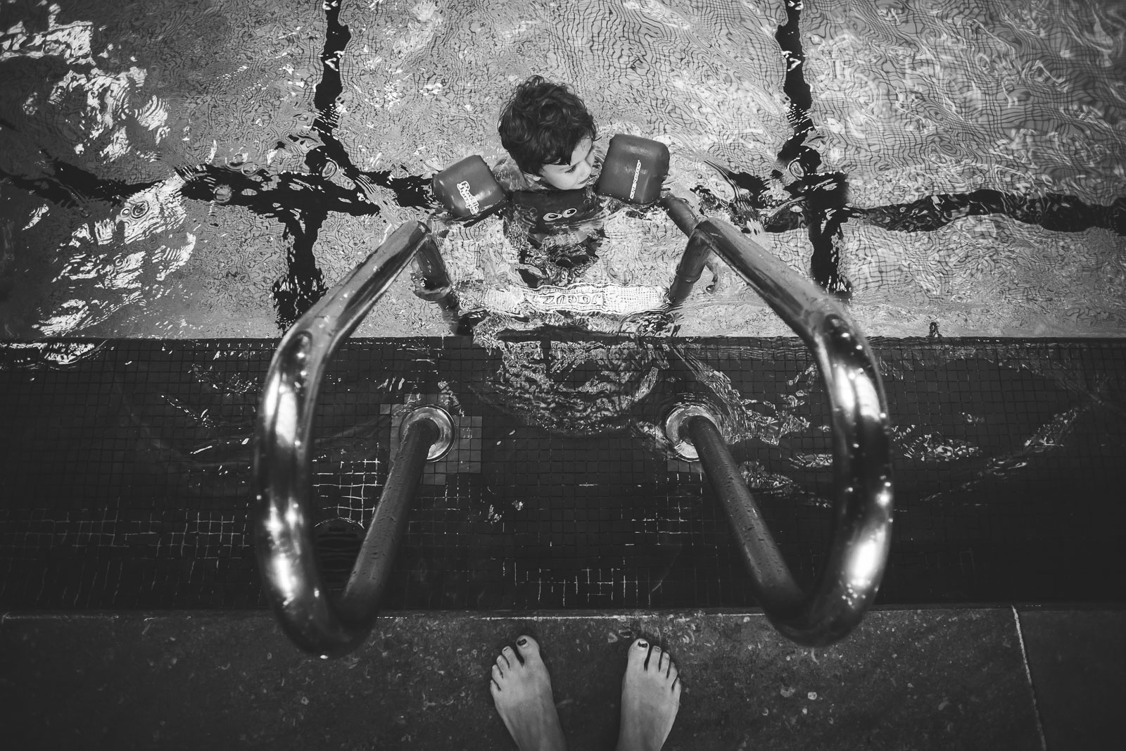child at edge of swimming pool with mothers feet close by myriam cobb