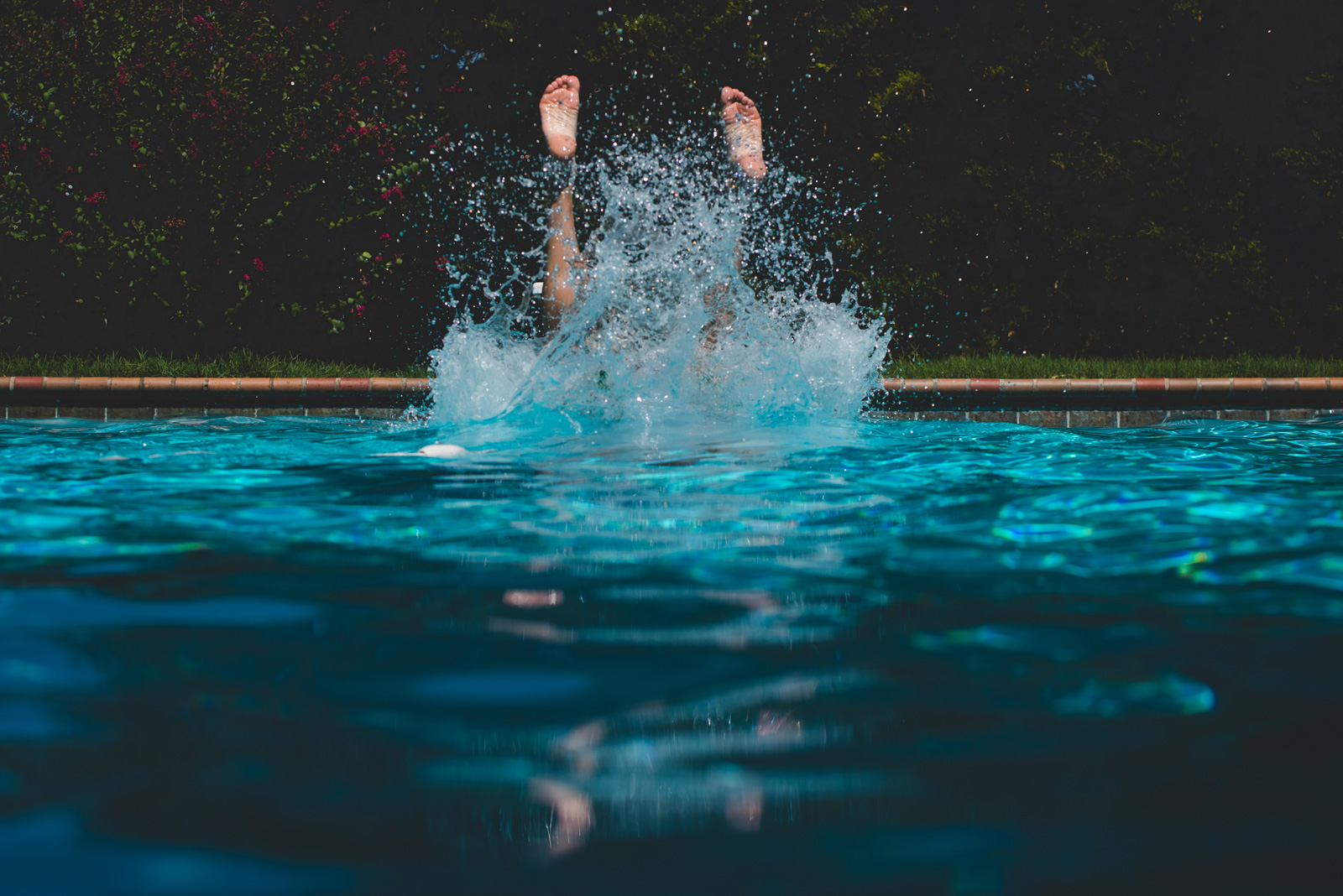 child diving into pool with feet in air water splashing by natalie greenroyd