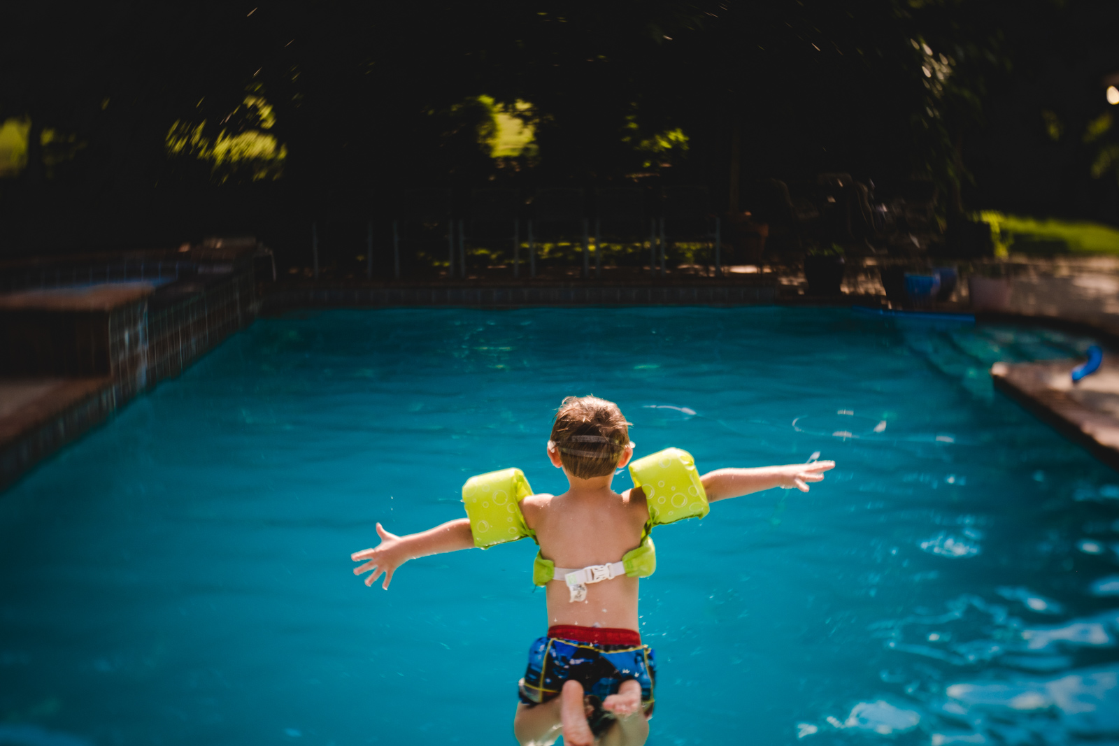 child with arms outstretched jumping into pool by natalie greenroyd