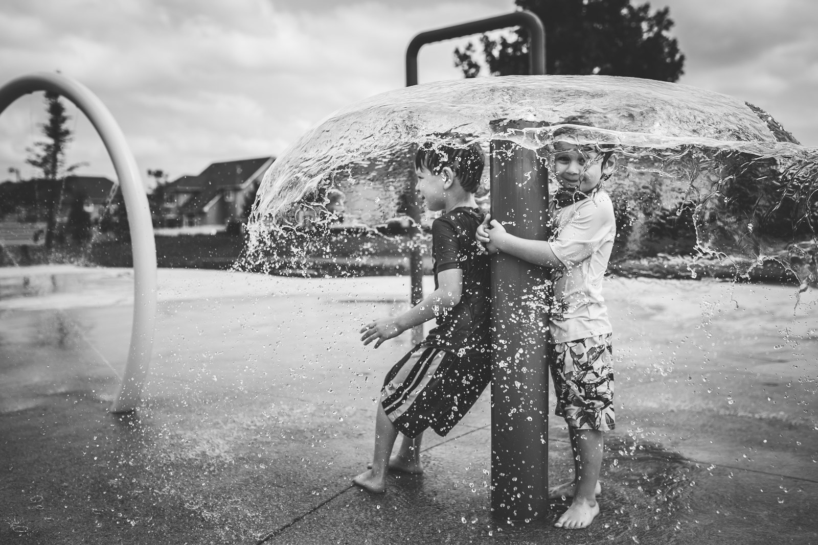 children playing in water fountain features outside black and white myriam cobb