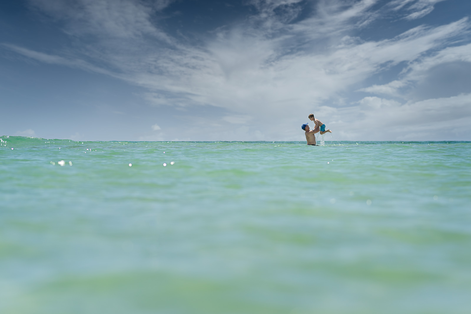 dad holding small boy up in air out of ocean water megan arndt clickin moms member story
