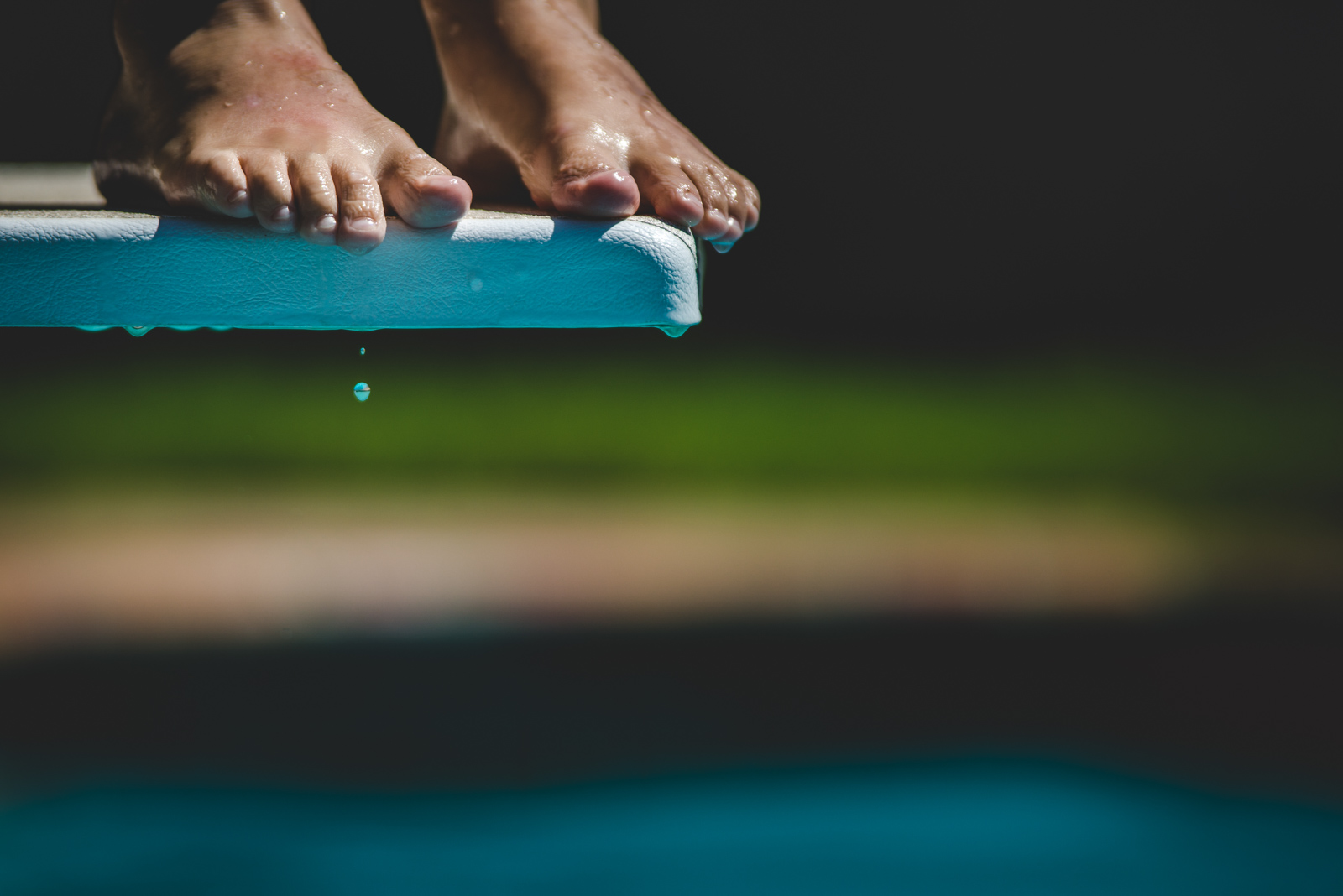 detail shot of feet on edge of diving board with water dripping off of toes by natalie greenroyd
