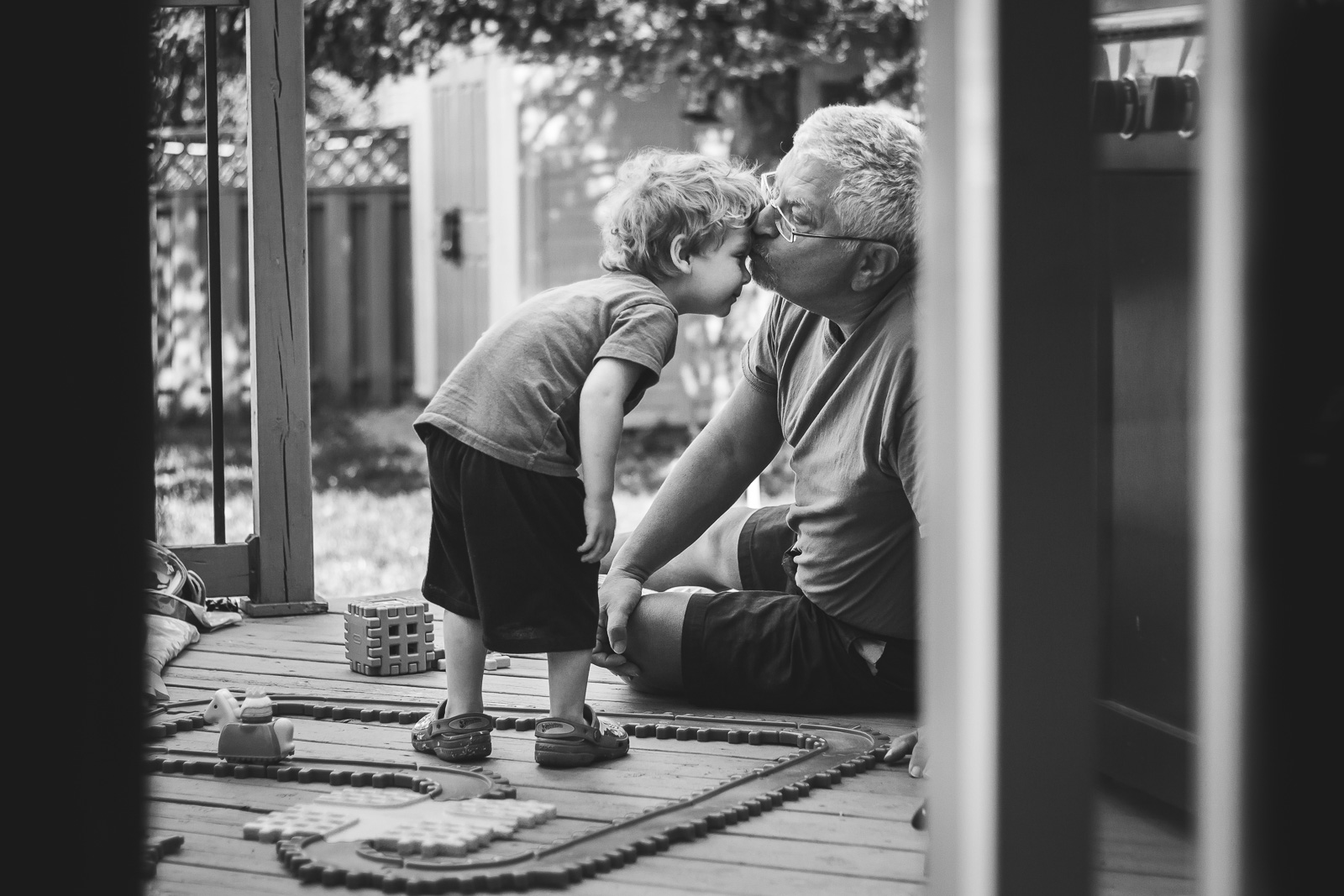 grandfather kissing grandson on forehead black and white myriam cobb