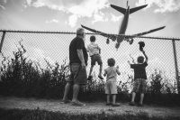 kids climbing fence with dad looking at jet land black and white Myriam Cobb