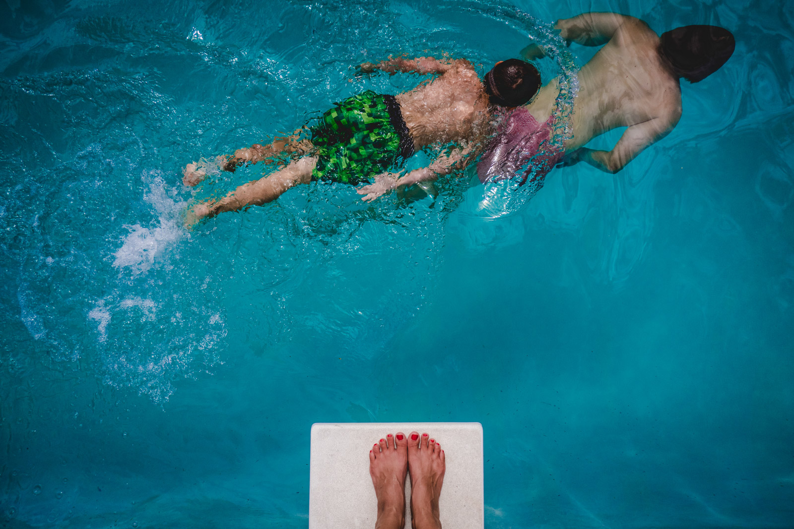 picture of manacured feet on diving board with kids swimming by underneath by natalie greenroyd