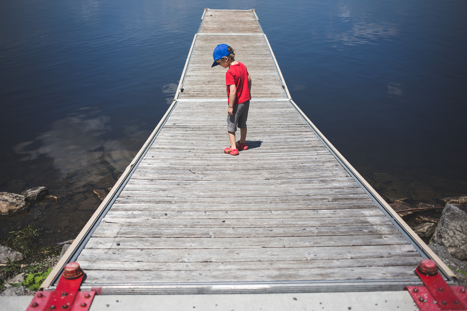 small boy in red shirt walking along dock by water myriam cobb