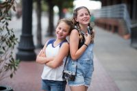 two tween girls laughing together on city sidewalk camera kristina mccaleb
