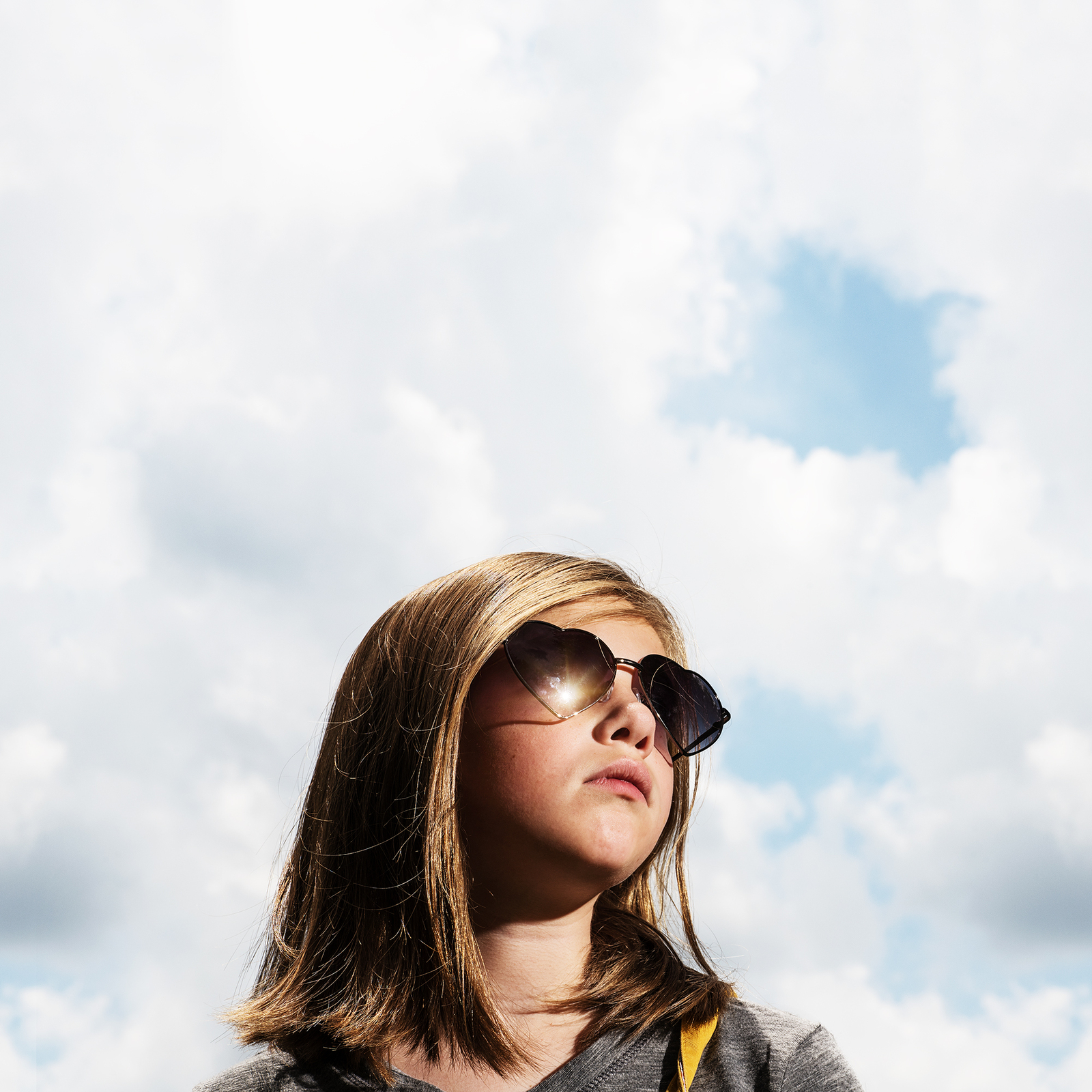 girl wearing sunglasses with blue sky in background
