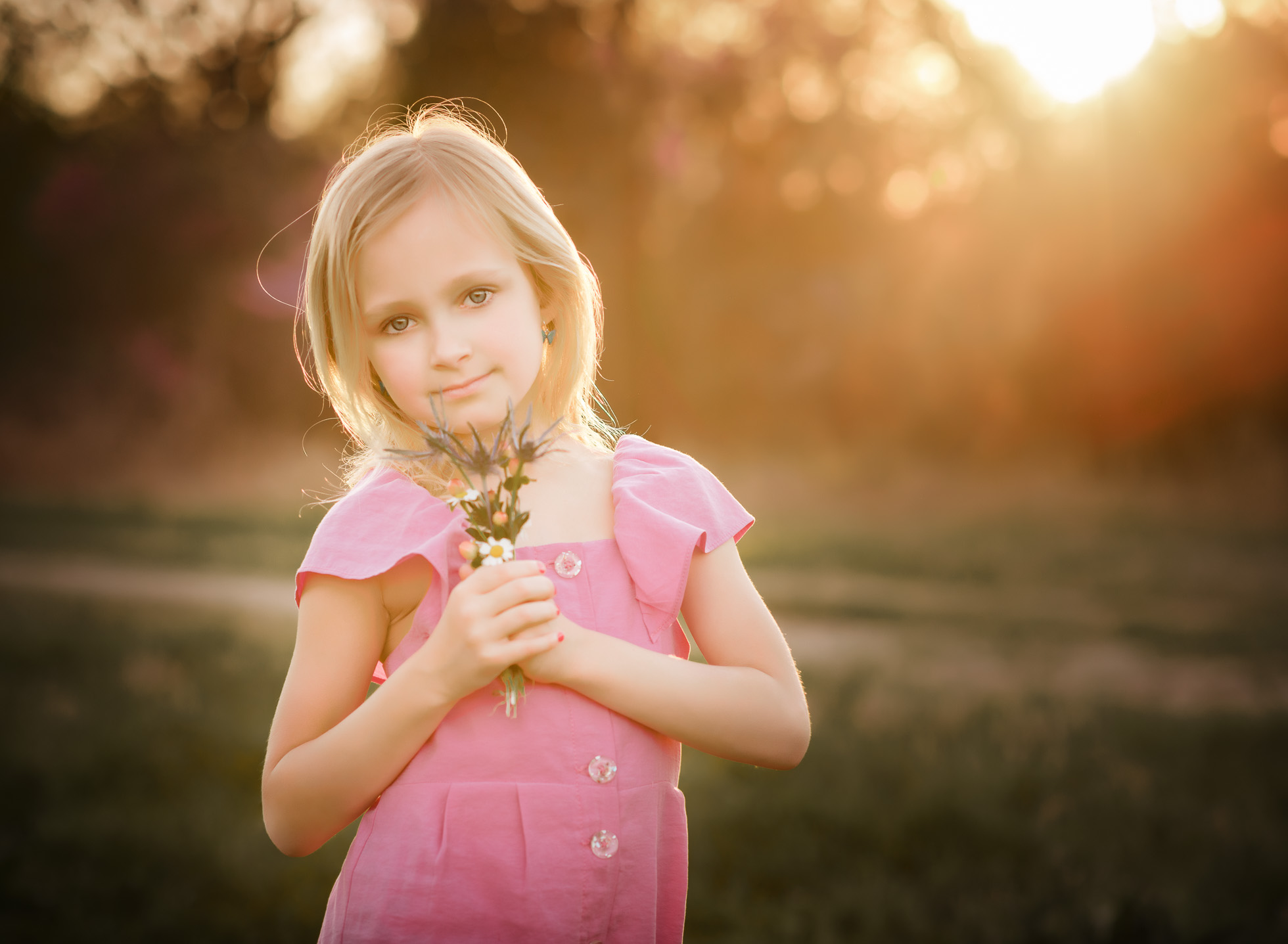 girl in pink shirt holding flowers after edit by kate luber