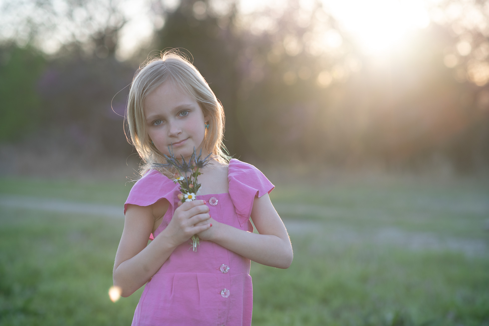 girl in pink shirt holding flowers before edit by kate luber