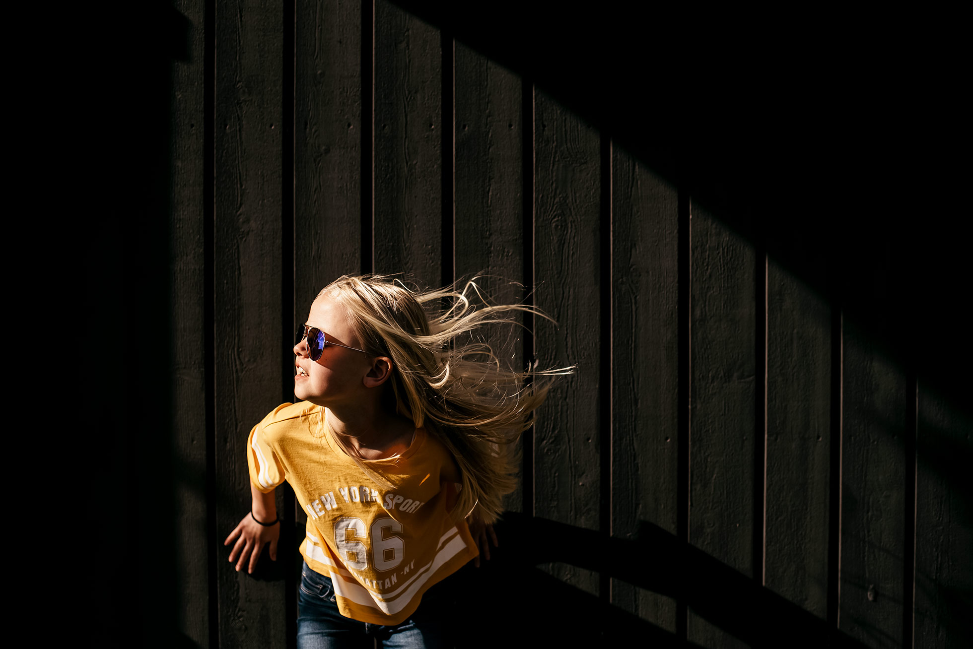 girl wearing sunglasses in light with wind blowing by jenny rosenbring