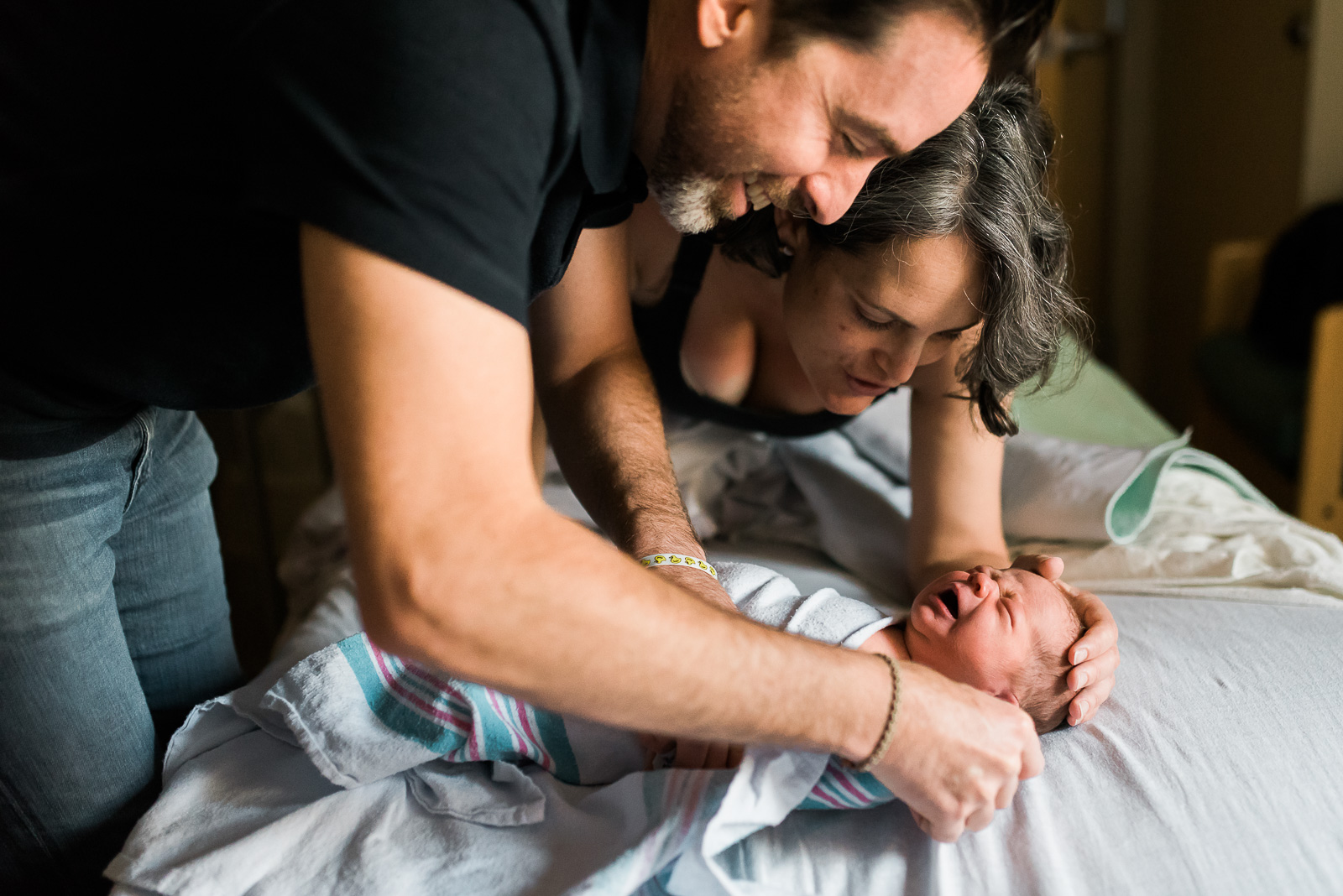 parents swaddling baby gazing with joy happy fresh 48 stacey adams