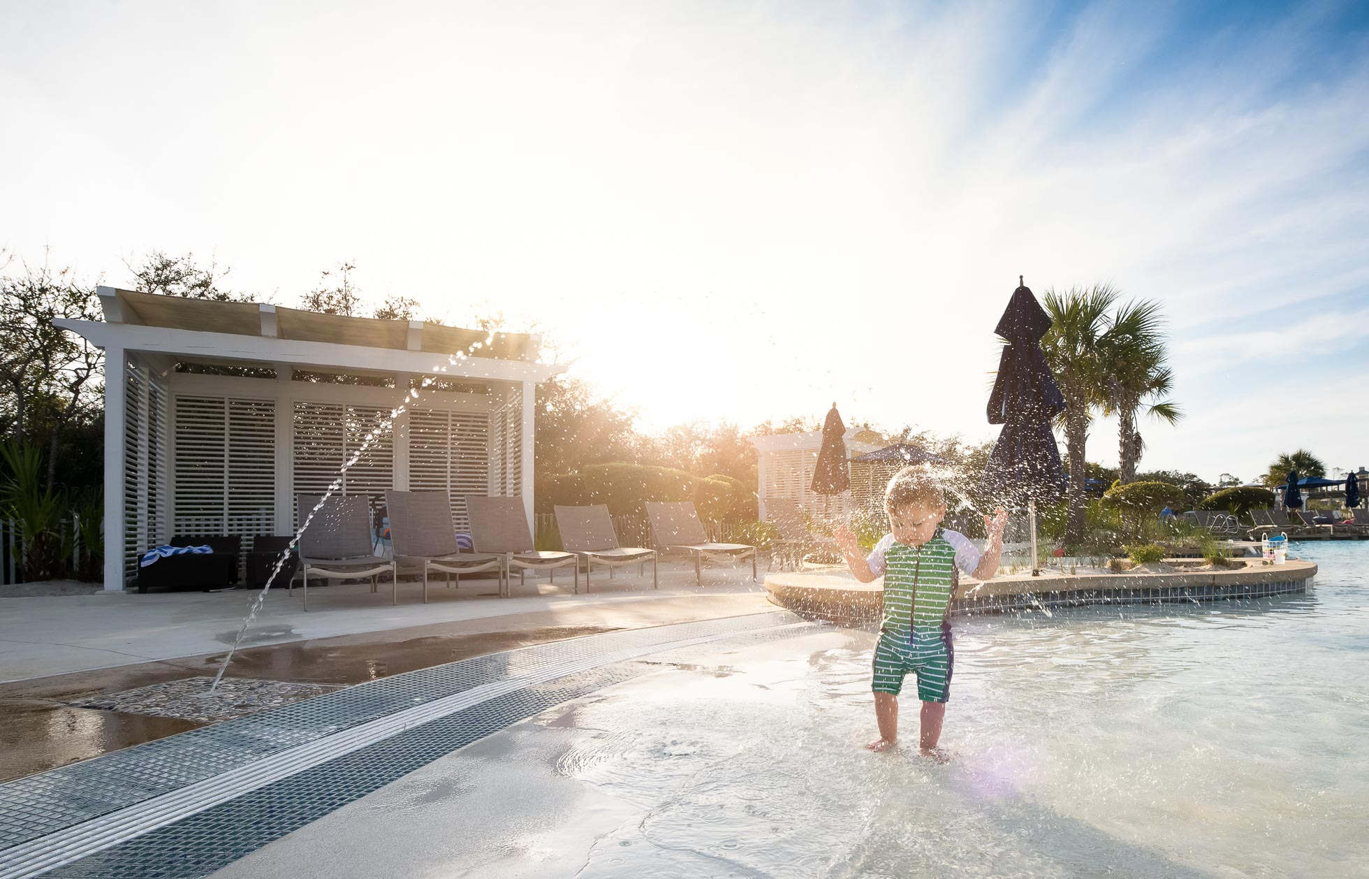 toddler palying in fountains at swimming pool summer after edit by megan arndt