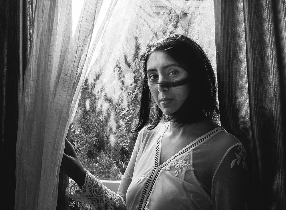 black and white photo of woman by window by jyo bhamidipati