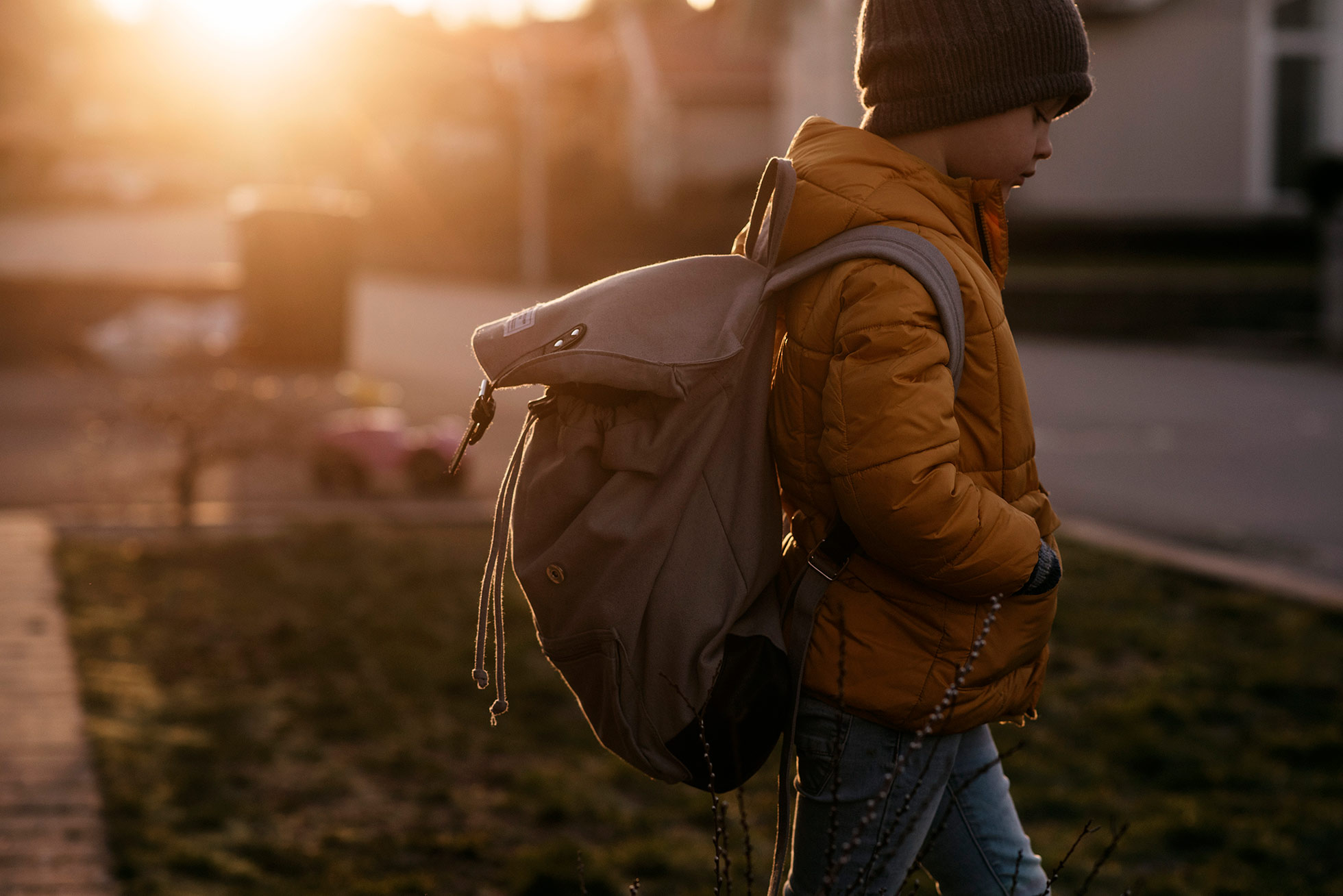 boy with backpack on his back with golden sun by jenny rosenbring