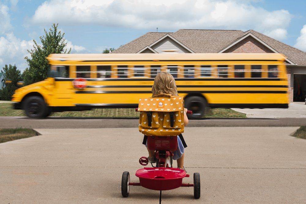 child on tricycle watching bus zoom by in a blur by jamie eilts