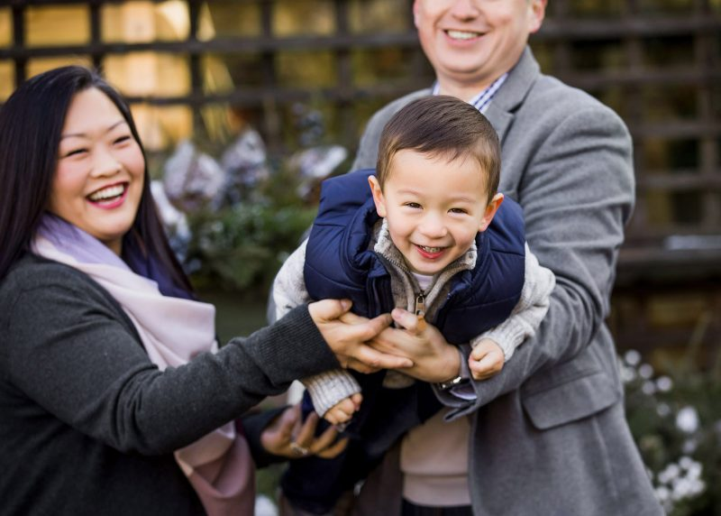 child smiling while parents hold him like an airplane games for happy family photos by leslie crane