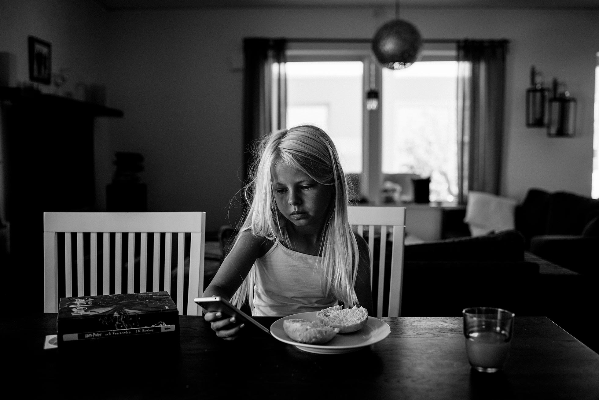 girl eating breakfast looking at phone by jenny rosenbring