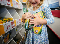 girl holding school supplies at store by kate luber
