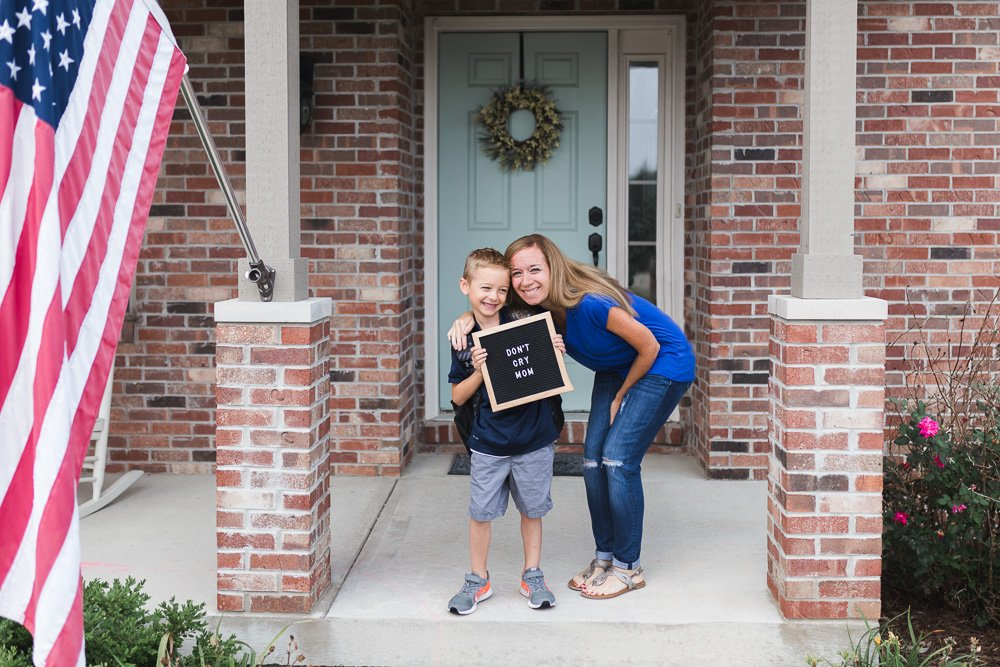mom with son holding back to school sign on front porch by jamie eilts