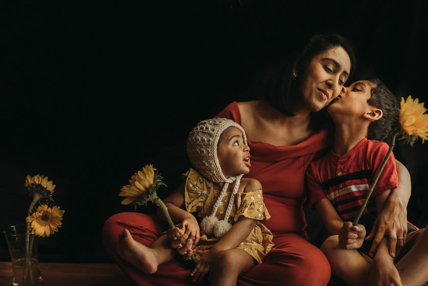 mother with children kissing her cheek flowers by jyo bhamidipati