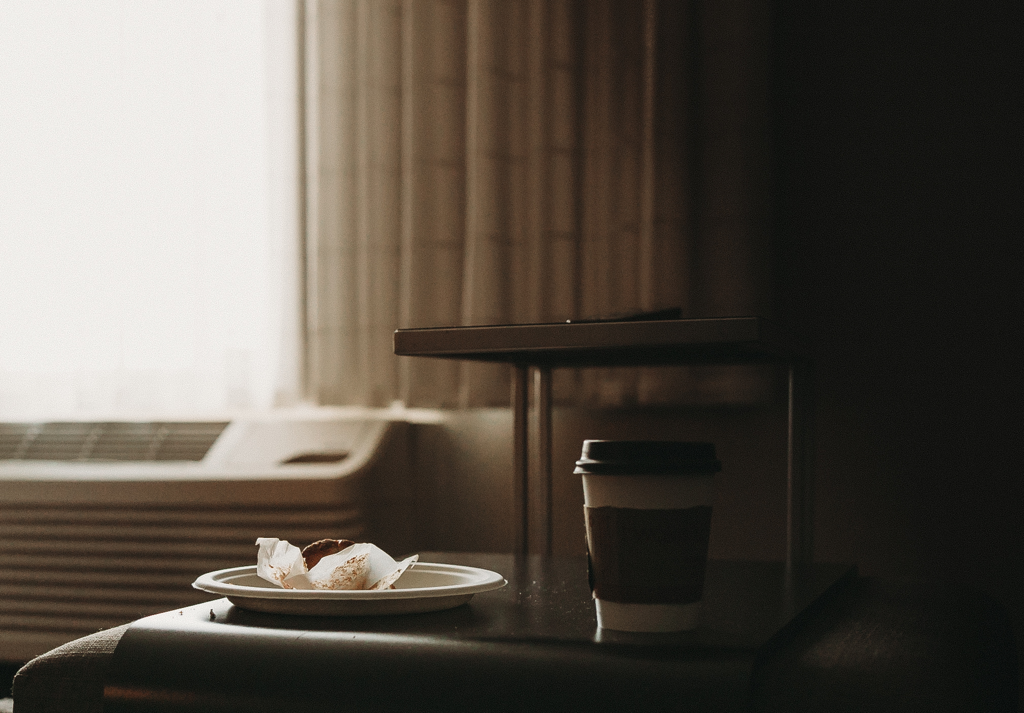 pastry wrapper and cup of coffee by window in low light by jyo bhamidipati