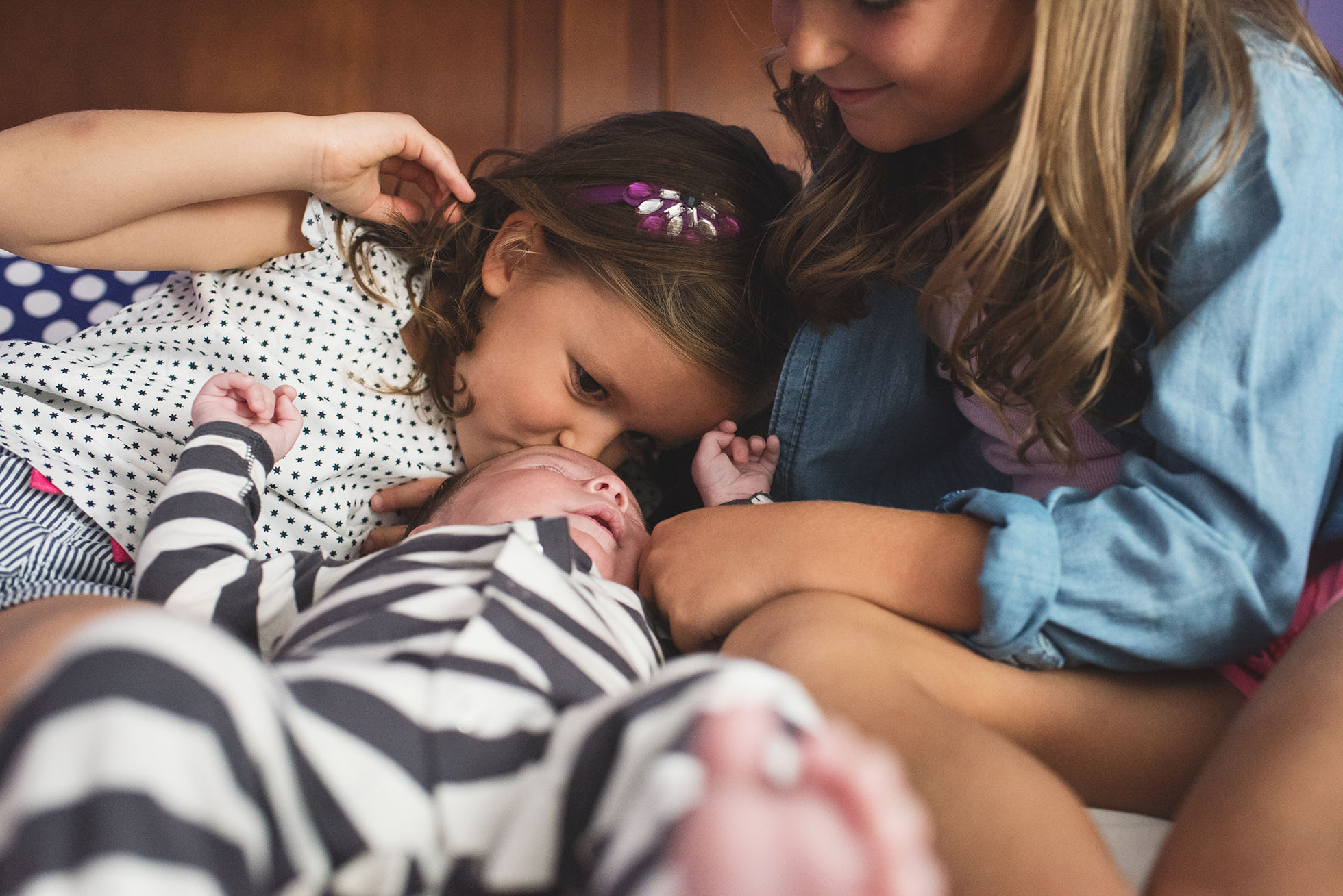 sisters with baby brother kissing his head kellie bieser