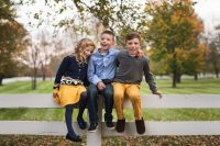 three kids sitting together on fence by kellie bieser