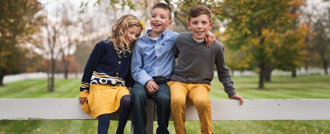 three kids sitting together on fence by kellie bieser