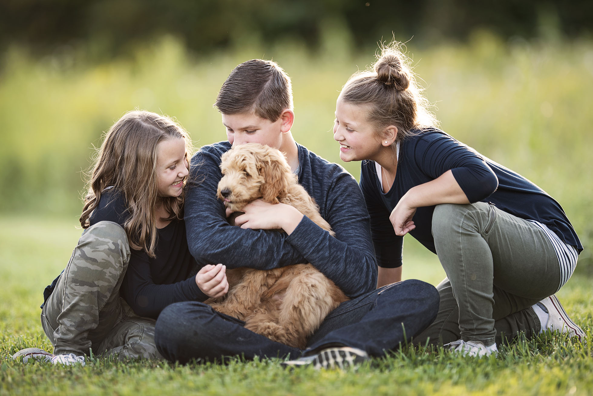 three kids with golden doodle puppy in grass by kellie bieser