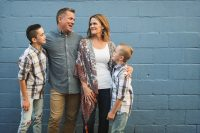 family standing in front of blue wall smiling at each other kellie bieser cmblog
