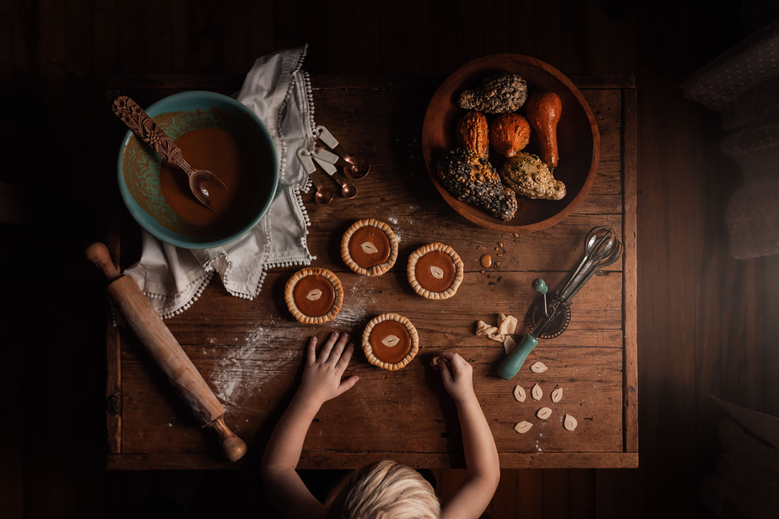 megloeks_11 small child at table making small pumpkin pies with gourds fall activities by meg loeks